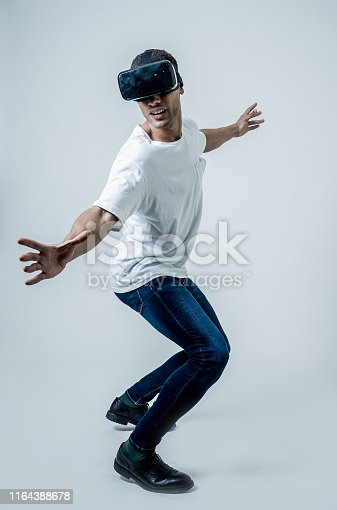 istock Amazed african american man surfing with augmented reality or VR goggles. Having fun riding on 3d simulated waves. In VR, new and futuristic technology experiences. 1164388678
