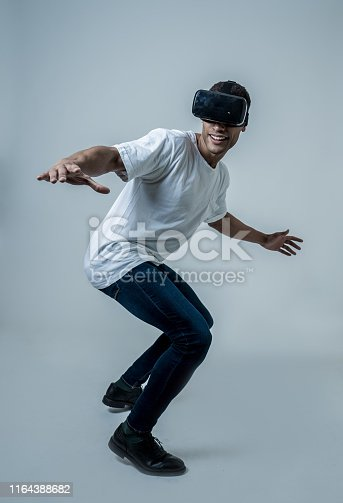 istock Amazed african american man surfing with augmented reality or VR goggles. Having fun riding on 3d simulated waves. In VR, new and futuristic technology experiences. 1164388682