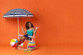 Beautiful African American woman sitting on a beach chair with colorful accessories and  umbrella in studio summer orange background with copy space