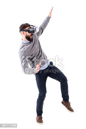istock Amazed bearded adult man having fun watching virtual reality glasses gesturing 931172498