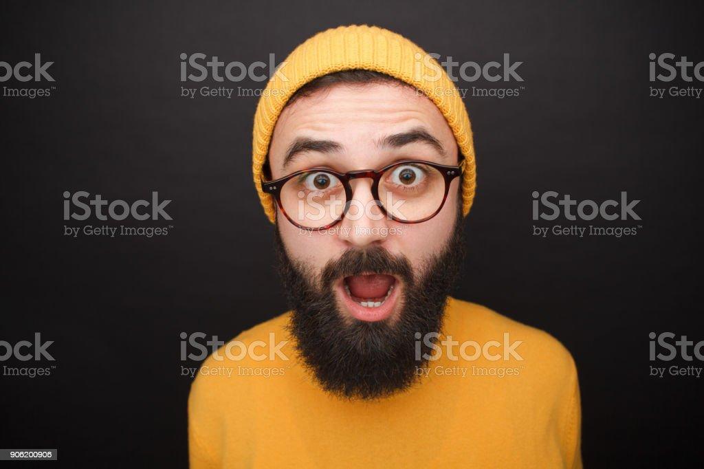 Amazed bearded man in yellow hat stock photo