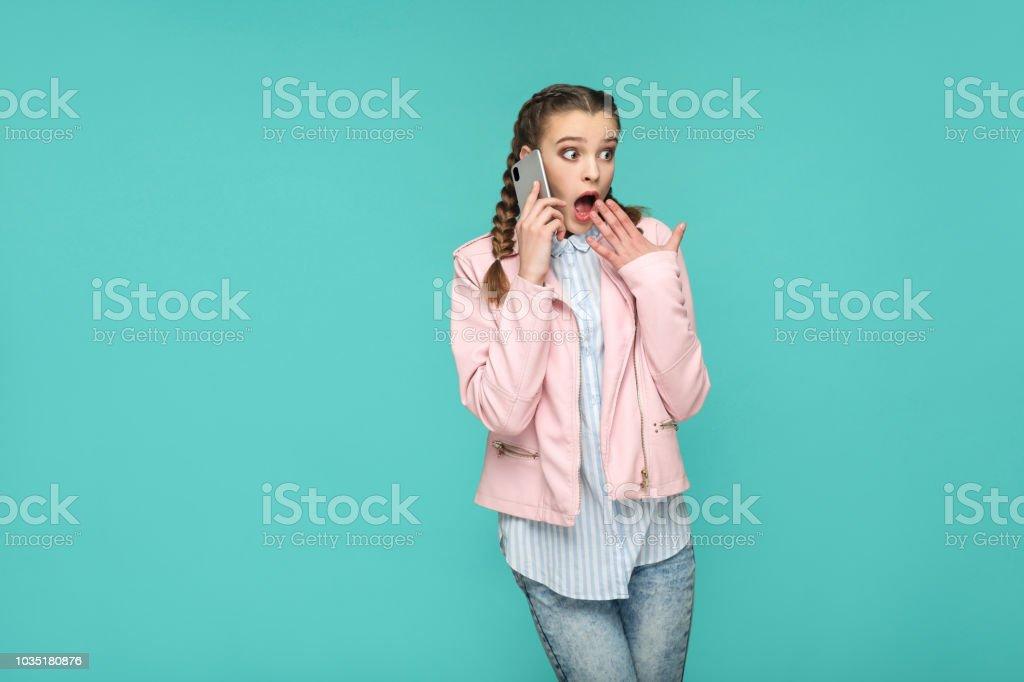 schönes Mädchen im casual-Stil, erstaunt Zopf Haare, stehen und sprechen auf mobile smart Phone und wegschauen mit schockiert Gesicht – Foto