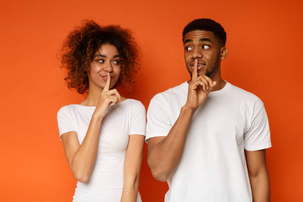 Amazed black couple make silence sign, keep forefingers on lips Shhh, it's our secret. Millennial african-american man and woman holding fingers on lips and looking at each other mysteriously, orange studio background finger on lips stock pictures, royalty-free photos & images