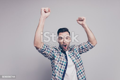 istock Amazed brunet guy with bristle in casual checkered shirt celebrating victory of favorite sport team with raised arms, cams,  shouting, screaming, yelling with open mouth on grey background 926558744