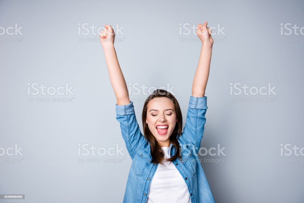 Amazed brunette young business woman in casual shirt is gesturing victory with her raised hands, she is shocked, extremely happy, with closed eyes, beaming smile, open mouth  on  grey background royalty-free stock photo