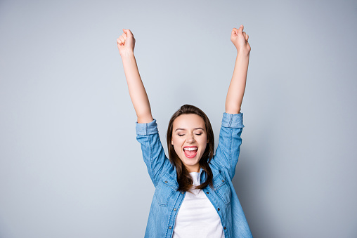 istock Amazed brunette young business woman in casual shirt is gesturing victory with her raised hands, she is shocked, extremely happy, with closed eyes, beaming smile, open mouth  on  grey background 926668568