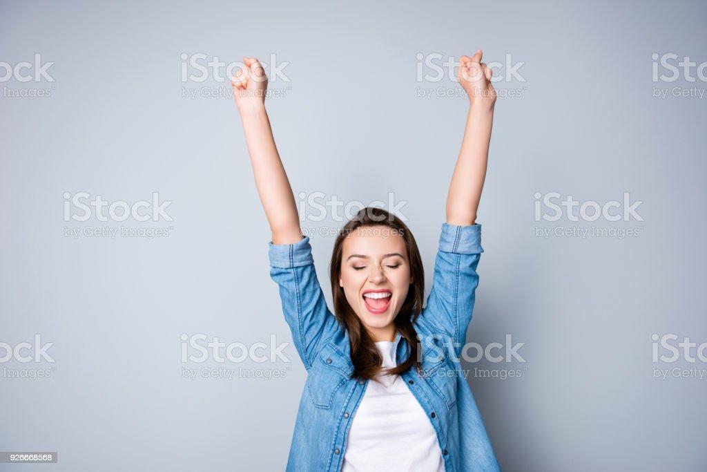Staunen Brünette junge Geschäftsfrau im lässigen Hemd gestikulieren Sieg mit erhobenen Händen, sie ist geschockt, sehr zufrieden, mit geschlossenen Augen strahlend Lächeln, offenen Mund auf grauem Hintergrund – Foto