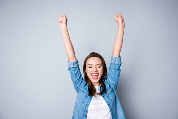 Amazed brunette young business woman in casual shirt is gesturing victory with her raised hands, she is shocked, extremely happy, with closed eyes, beaming smile, open mouth  on  grey background stock photo