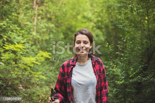 Centered view of a young woman on her hike throughout the dense woods. It's gonna be a long walk to the top.