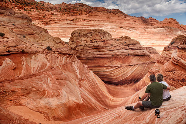 Amazed by the Wave A male tourist hugs his female companion as they overlook the spectacular sandstone rock formations known as the Wave located within the Paria Canyon-Vermilion Cliffs Wilderness, Page, Arizona, US, North America page arizona stock pictures, royalty-free photos & images