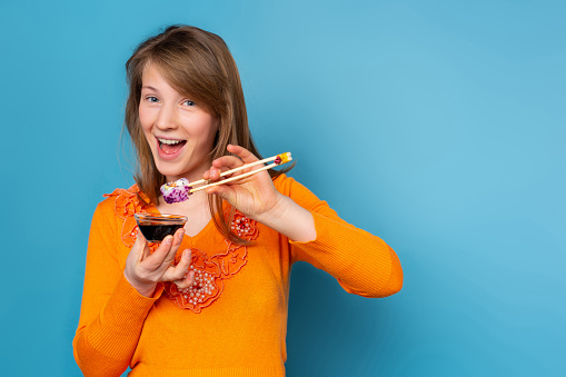 Amazed caucasian blonde girl eating japanese roll with bamboo beginner training sushi chopsticks, holding bowl with soy sauce on blue background. High quality photo