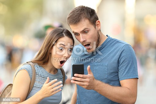 istock Amazed couple watching on line media in a phone 856974548