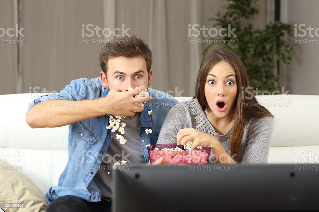 Amazed couple watching tv stock photo
