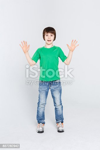 istock Amazed cute little boy showing his palms on white studio background 837282942