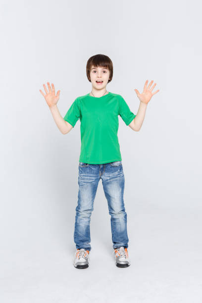 Amazed cute little boy showing his palms on white studio background stock photo