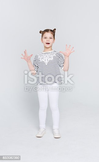 istock Amazed cute little girl showing her palms on white studio background 832082392