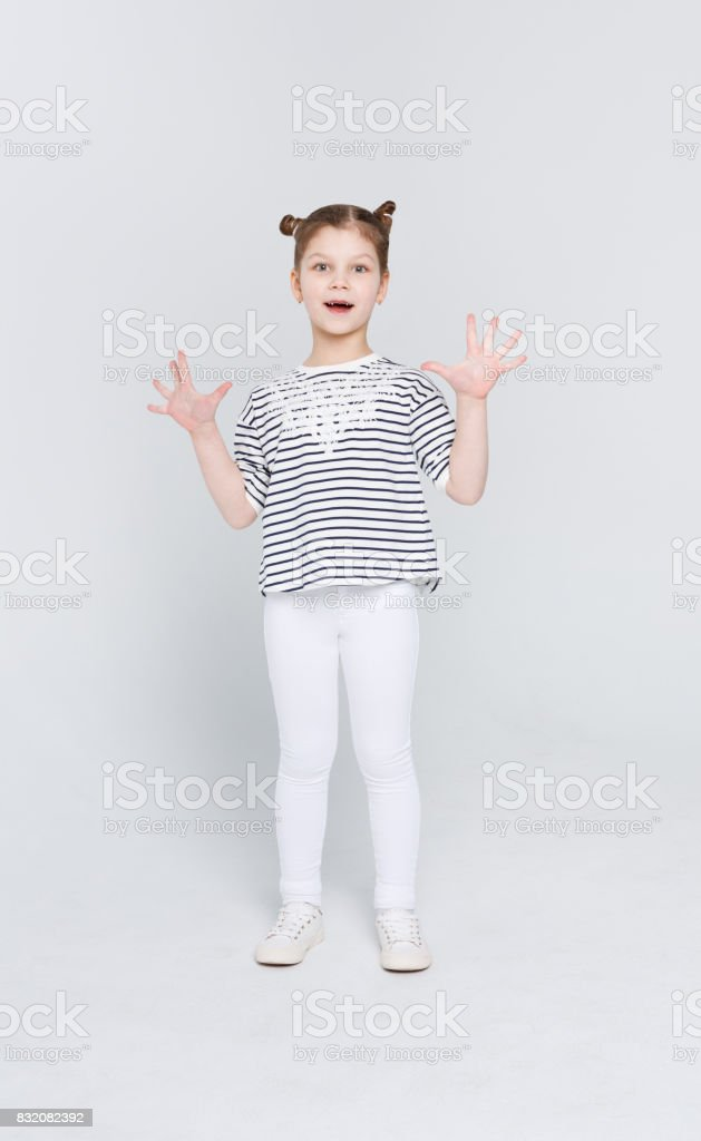 Amazed cute little girl showing her palms on white studio background stock photo