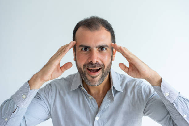 amazed emotional middle-aged man touching head in excitement - excited emoji stock photos and pictures