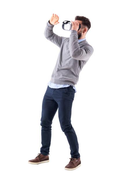 Émerveillé d'excitée jeune homme adulte tenant vr lunettes et gesticulant avec main - Photo