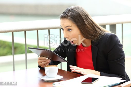 istock Amazed executive receiving good news in a tablet 833161768