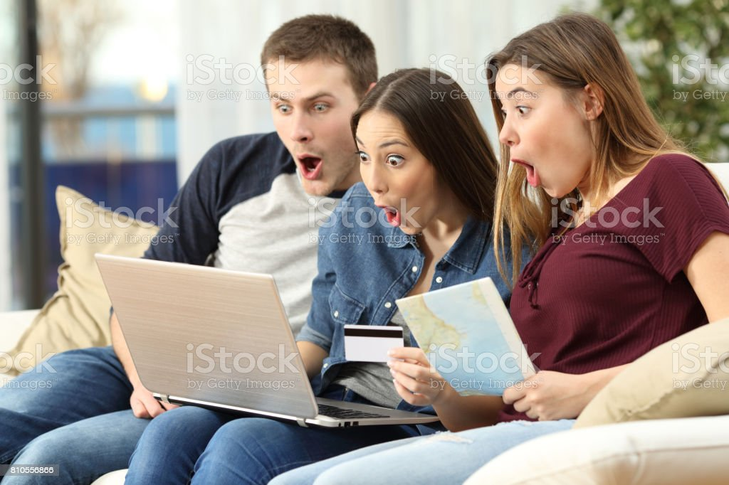 Amazed friends finding trip offers on line stock photo
