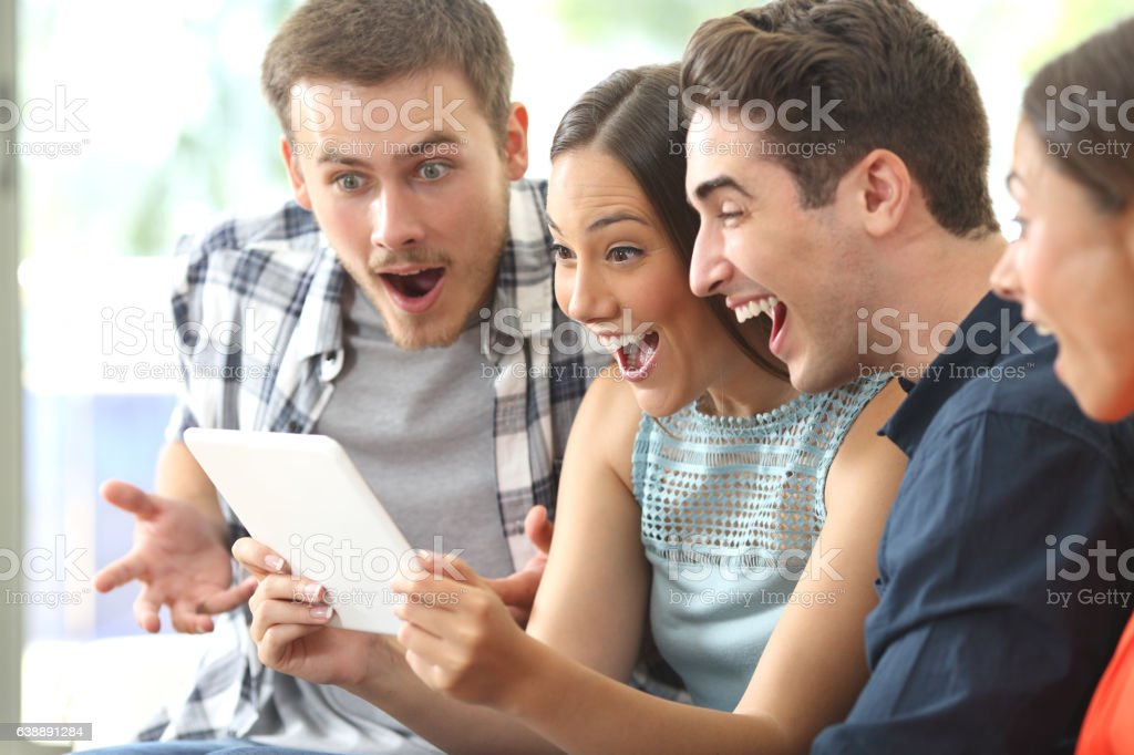 Amazed friends watching media in a tablet - foto de stock