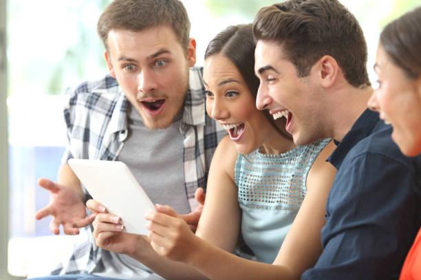 Amazed friends watching media in a tablet - foto de stock