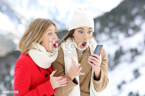 istock Amazed friends with a smart phone in winter 896820268
