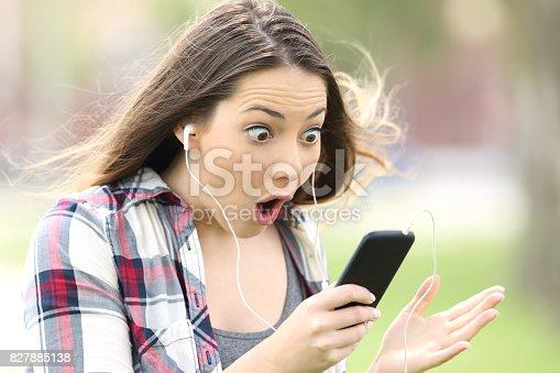 istock Amazed girl listening on line music 827885138
