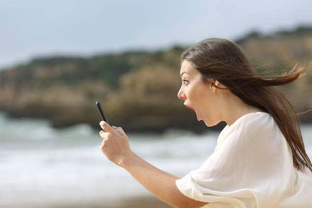 Amazed girl with her smart phone stock photo