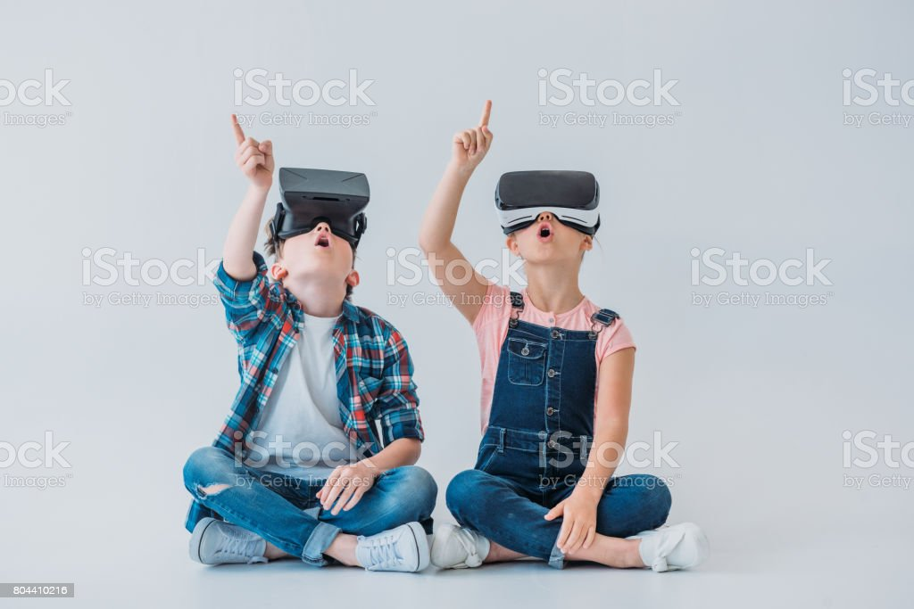 amazed kids using virtual reality headsets and pointing up with finger while sitting on the floor stock photo
