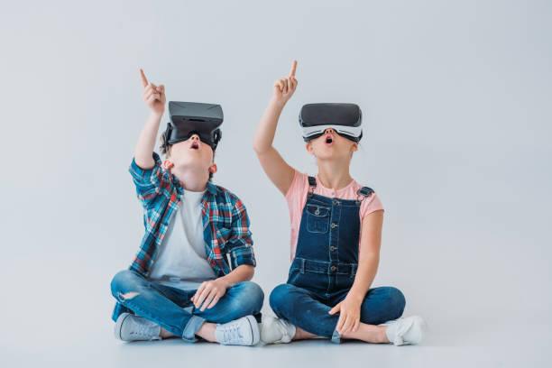 仮想現実のヘッドホンを使用して、床に座りながら指で上向き驚く子供たち ストックフォト