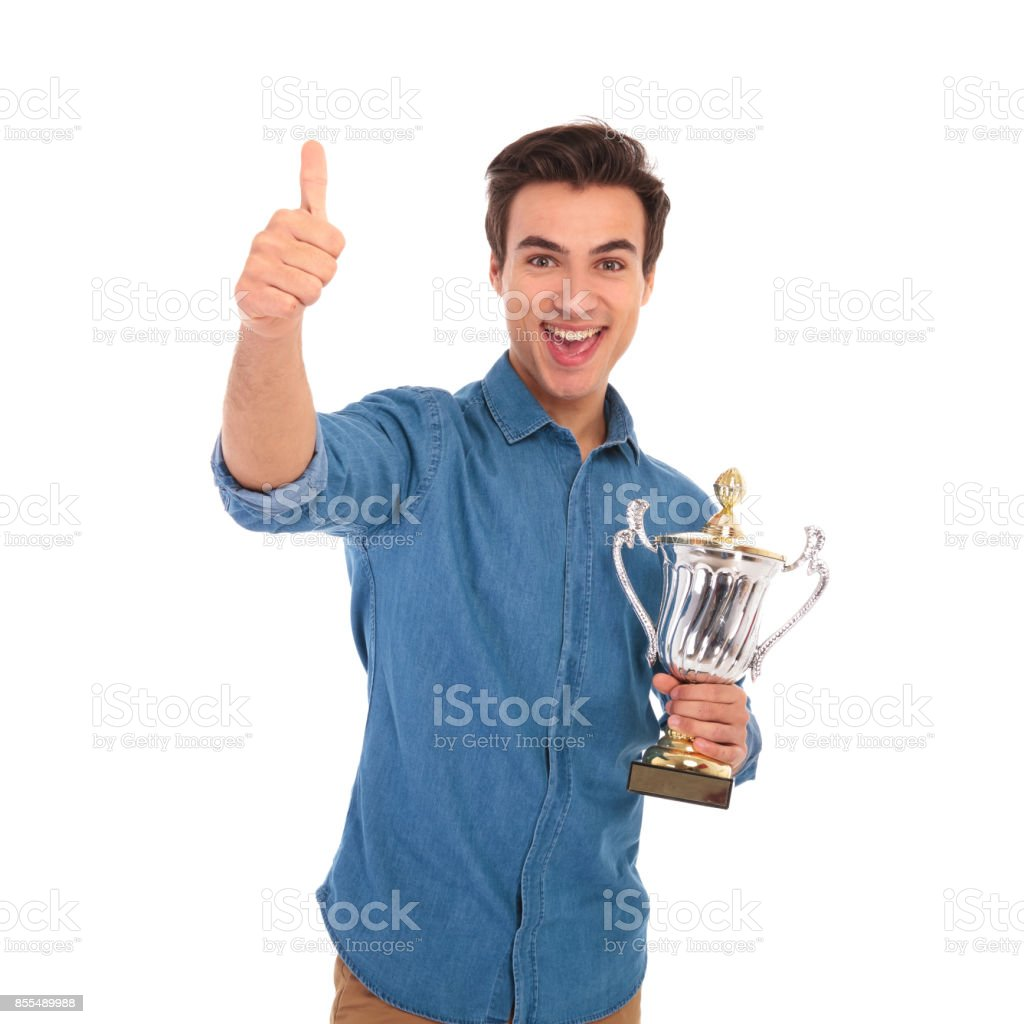 amazed man holding trophy cup and makes the ok sign stock photo
