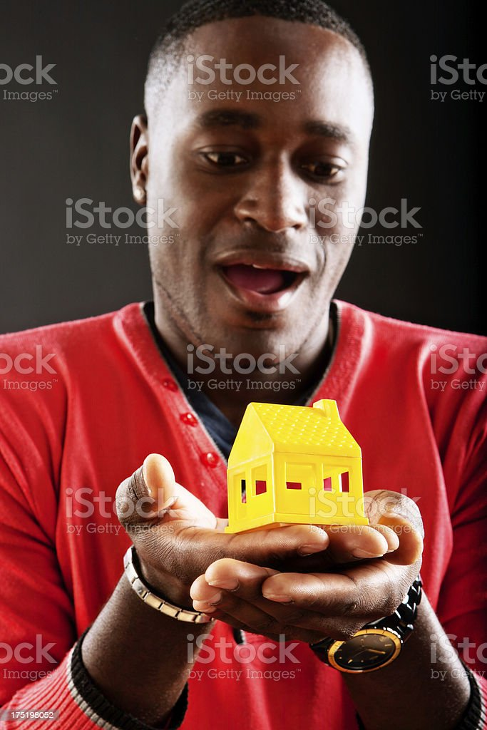 Amazed man looks down a yellow toy house stock photo