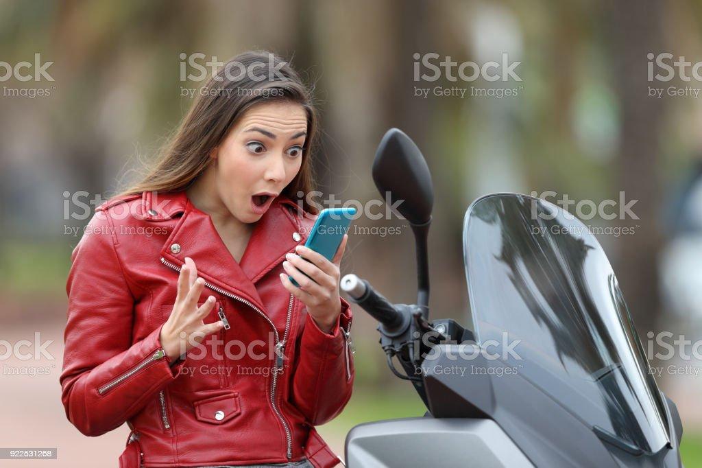 Amazed motorbiker reading exciting news on line stock photo