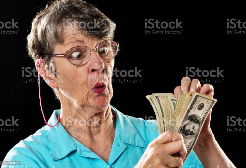 Amazed old woman counting thick sheaf of dollars, wide eyed stock photo