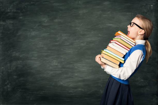 Amazed School Girl Holding Many Books, Astonished Strong Child on Blackboard, Hard Education stock photo