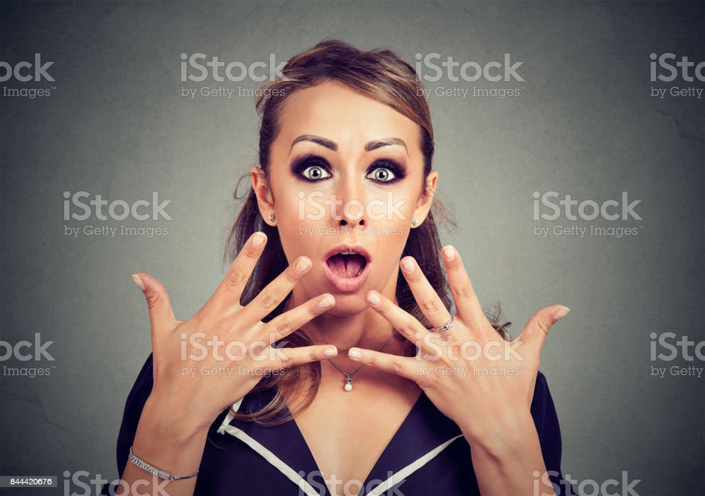 Amazed shocked woman looking at camera isolated on a gray background stock photo