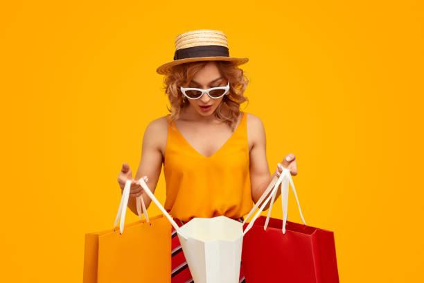Amazed shopaholic looking inside paper bag stock photo
