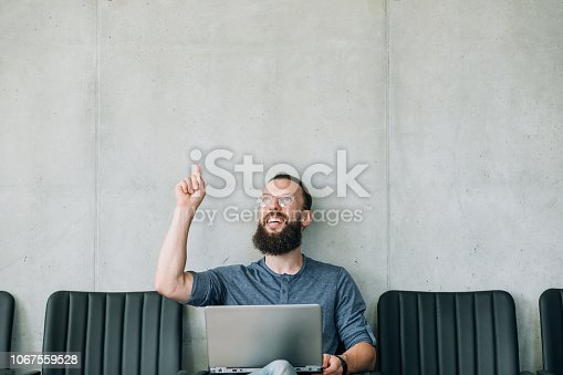 inspired amazed smiling man pointing index finger upward. office business employment concept. empty space for advertisement.
