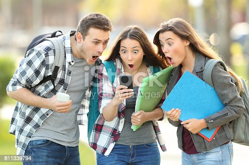 istock Amazed students checking content on a phone 811339794