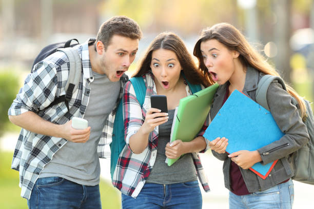Amazed students checking content on a phone stock photo