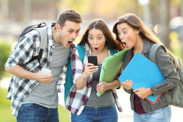 estudantes espantados, verificando o conteúdo em um telefone - happy test results - fotografias e filmes do acervo