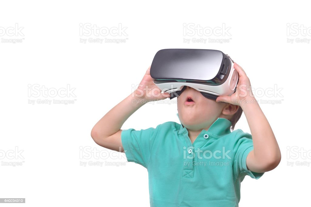 Amazed teen boy wearing virtual reality goggles watching movies stock photo