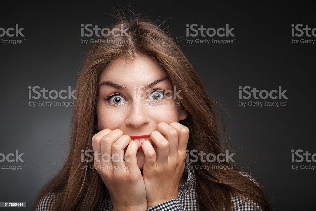 Amazed woman biting nails. stock photo