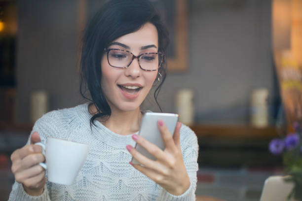 Amazed woman checking phone finding good news