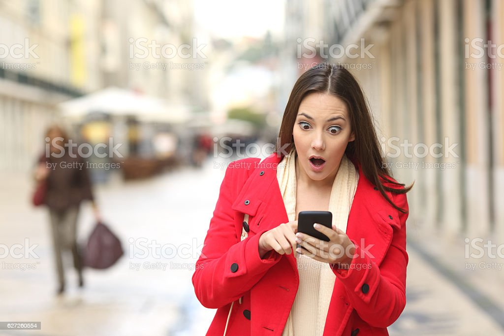 Amazed woman checking smart phone in the street - Photo