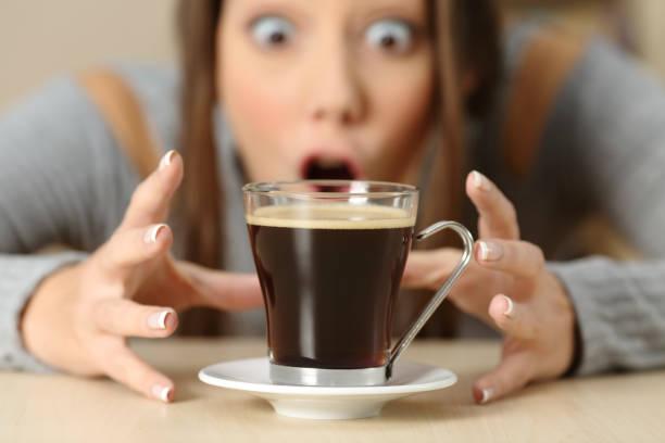 förvånad kvinna som tittar på kaffekoppen - koffein bildbanksfoton och bilder