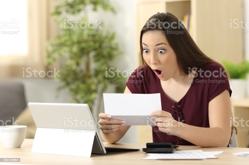 Amazed woman reading good news in a letter stock photo
