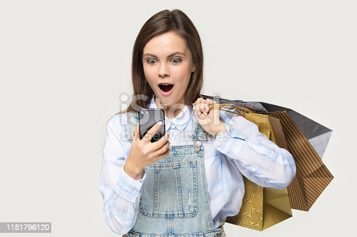 istock Amazed woman shopper holding shopping bags looking at smartphone screen 1151796120